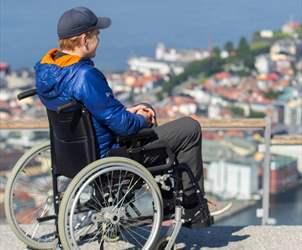 Handikappvennlige attraksjoner og museer i Bergen - gutt i rullestol ser utover Bergen fra Fløyen