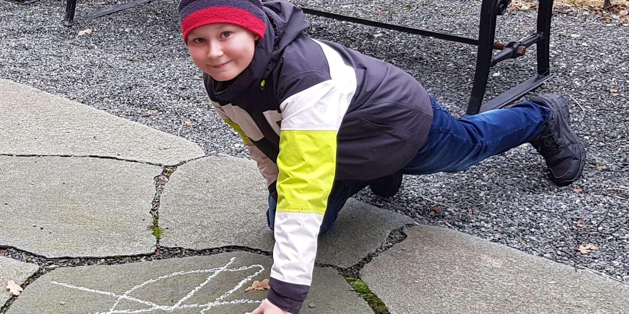 Gutt tegner bumerke med kritt
