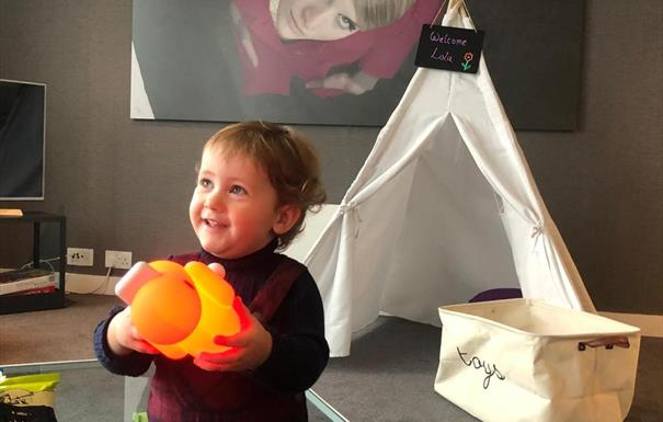 child holding light up toy in a staying cool rotunda apartment with toybox in the background