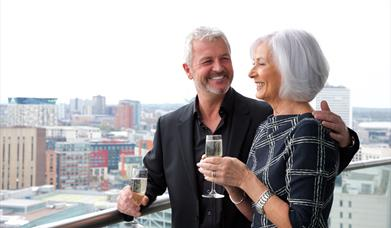 A couple enjoying their September Staycation city views on Staying Cool's Rotunda apart hotel top floor balcony