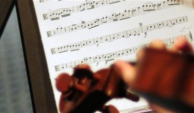 A close-up of sheet music, with a violin in the foreground.