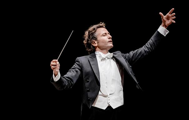 Conductor Gustavo Gimeno holds a baton and his arms aloft. His eyes are closed and he is wearing white tie.
