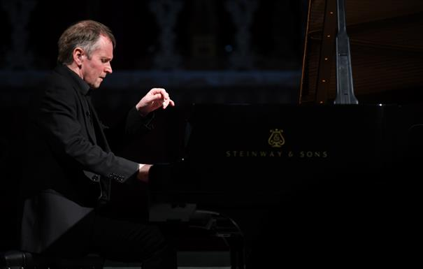 Pianist Steven Osborne is playing a piano. He wears a black shirt and jacket.