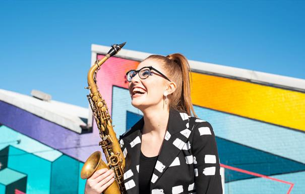 Jess Gillam is smiling broadly, holding her saxophone. Her red hair is tied up in a ponytail, and she is wearing black glasses. Behind her, there are
