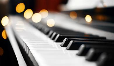 A photo of piano keys, with sparkling lights in the background.