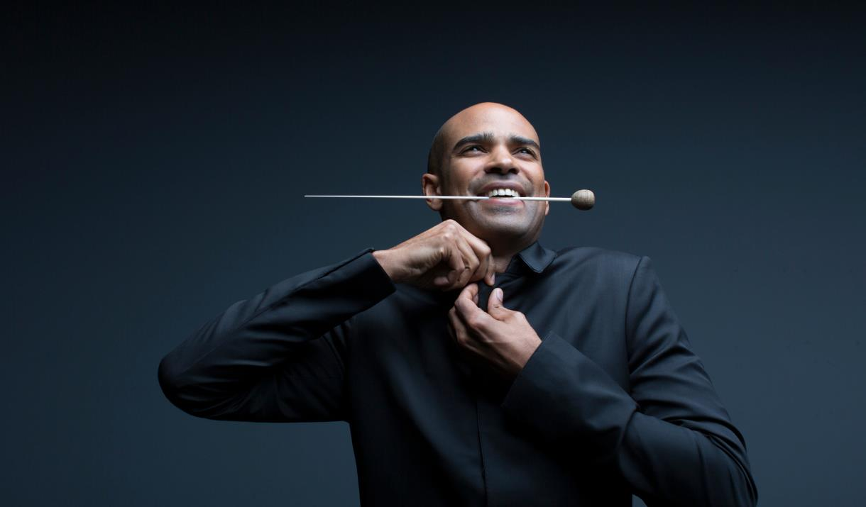 The conductor Kevin John Edusei stands holding his baton between his teeth as he fastens the top button of his black shirt.