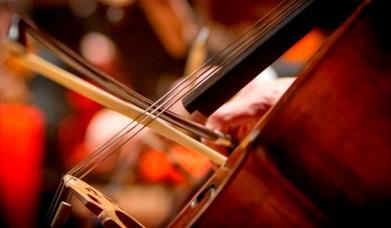 A close-up photograph of a cello, showing the bow being pulled across the strings.