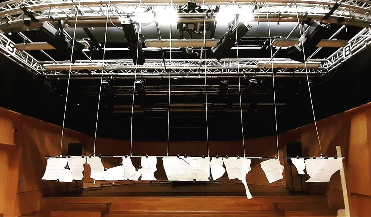 fragments of paper with musical notation hang from a lighting rig in a concert hall