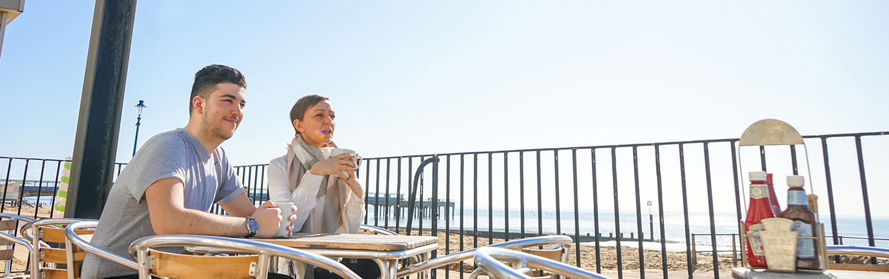 Man and woman holding a coffee and eating food overlooking the sea and pier