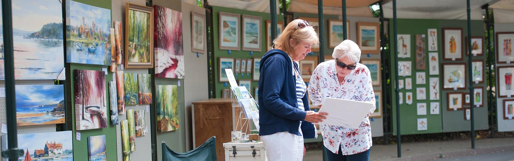 Two women exploring the Pine walk market in Bournemouth