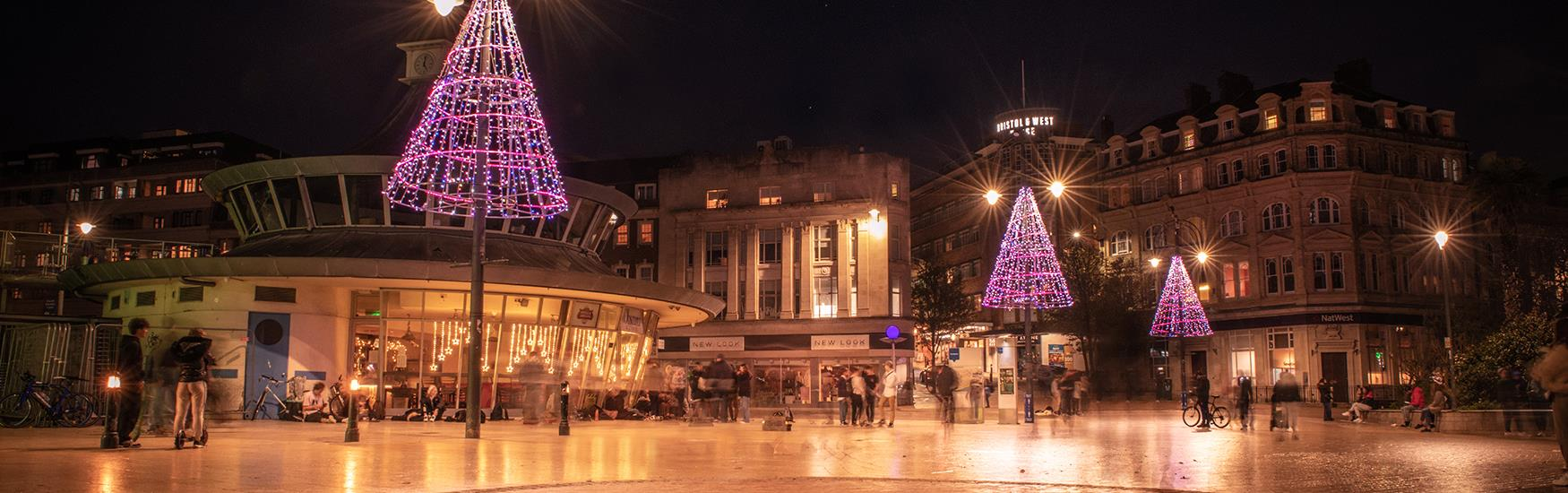 Town Square decorated with Christmas lights and festive decorations with shops in the background
