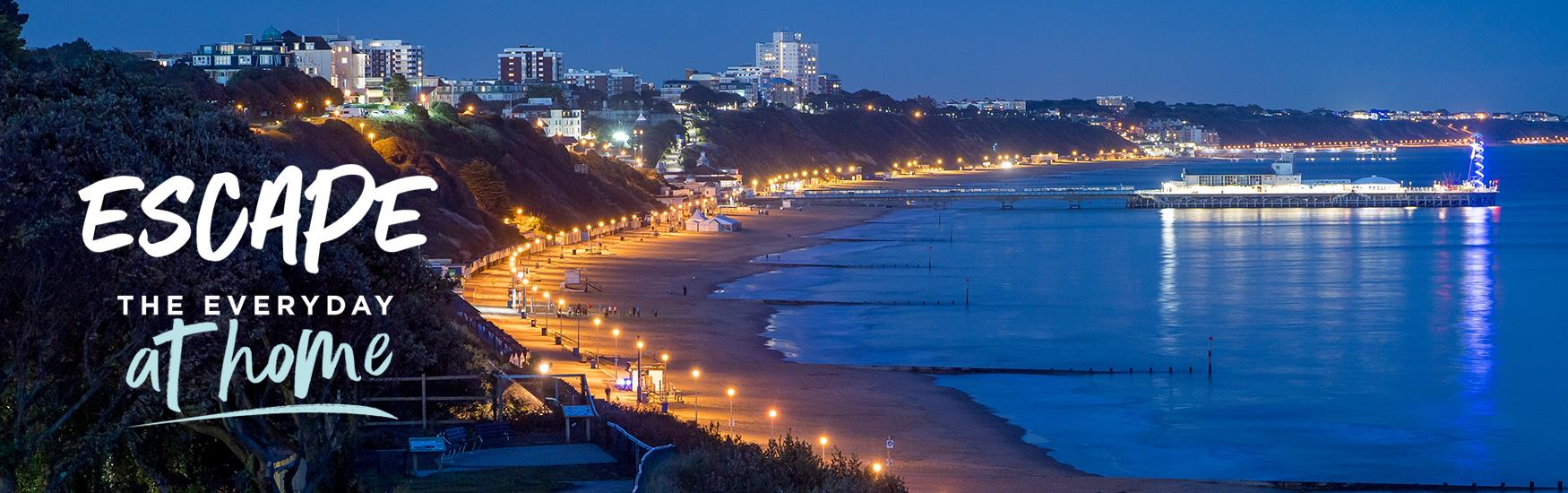 Bournemouth Bay lit up at night with the text Escape the Everyday at home
