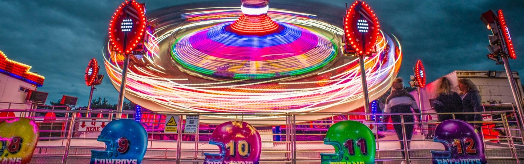 Neon lights illuminate the spinning ride at the funfair in Bournemouth