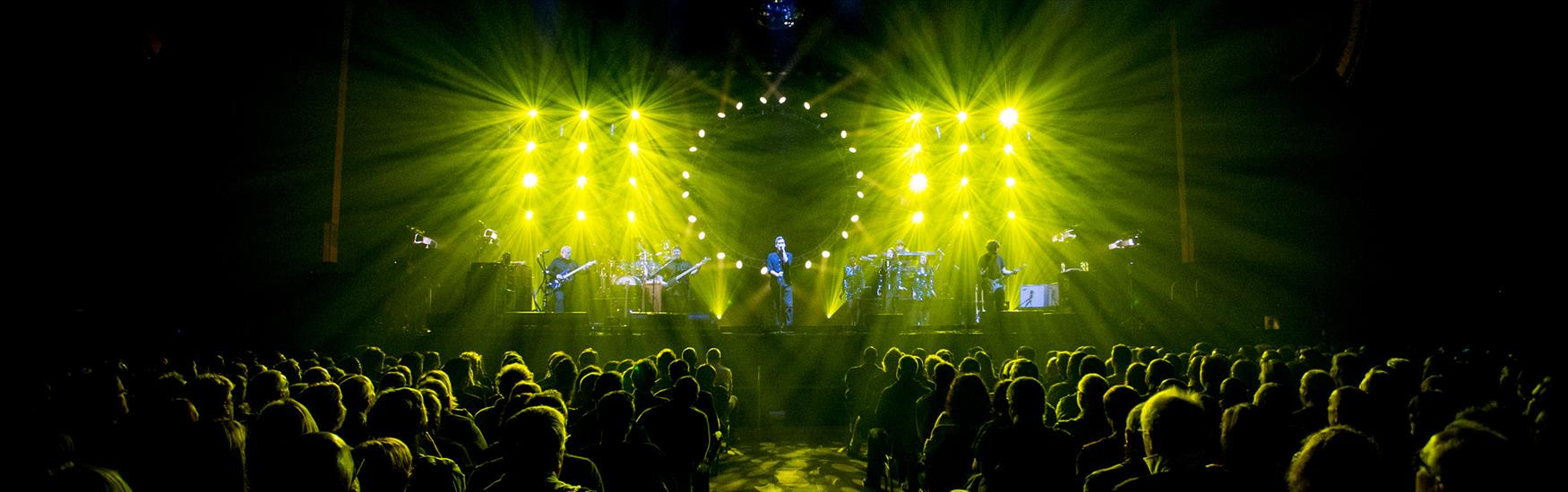band performing live at the Bournemouth International Centre with green light shining behind