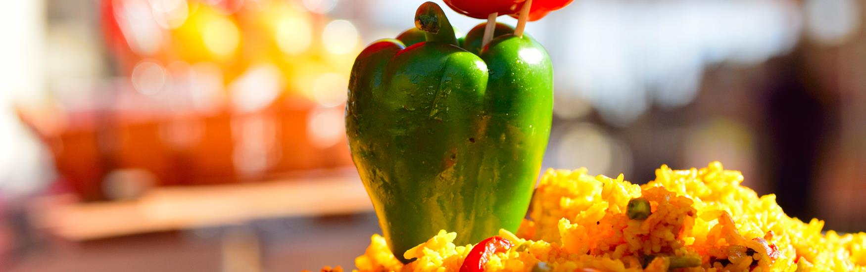 A paella prepared with pepper garnish - food and drink experiences