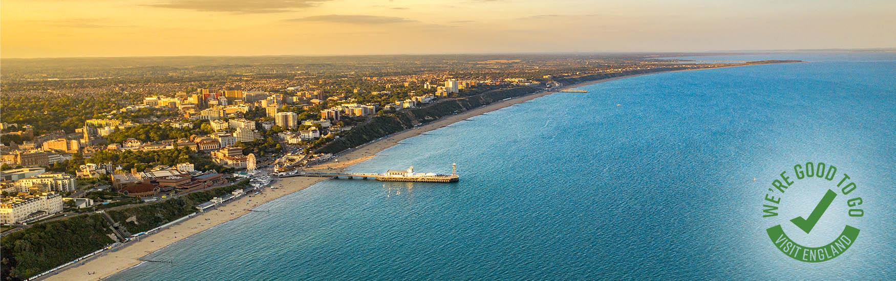 Sunset image of Bournemouth Bay beach and clifftops with green we're good to go logo in the corner
