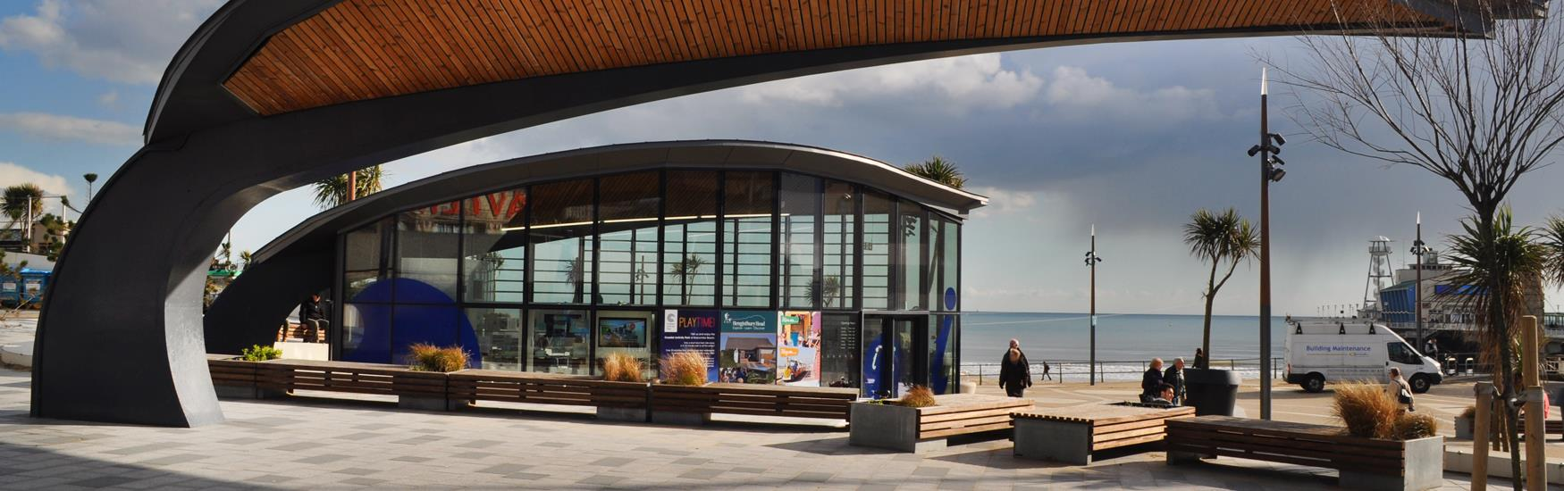 View of Pier Approach area with glass building and the pier and the sea in the background on a summer's day