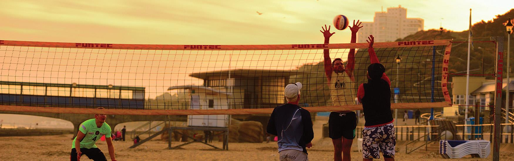 men playing volleyball on the beach with a stunning sunset on Bournemouth Beach