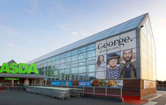Exterior of the ASDA superstore with George clothing poster in glass atrium.