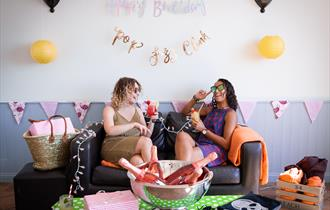 Two venue guests laughing and drinking on a sofa inside the decorated venue