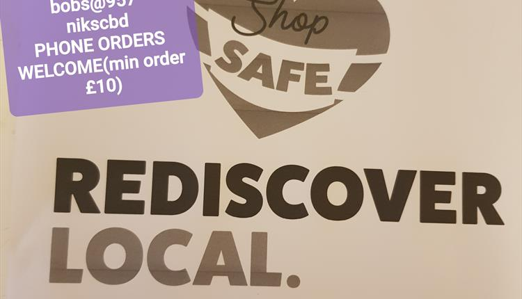 Purple sticker with shop information over a brown poster with shop safe, rediscover local logo.