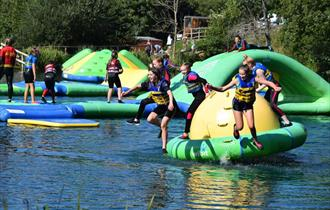 Children jumping off equipment into the water