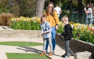 Mother and two children playing golf in Bournemouth Gardens