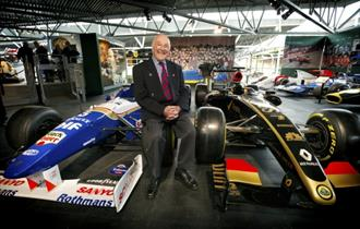 Murray Walker leaning on a racing car