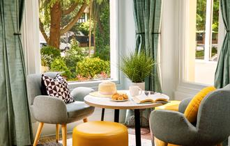 Seating area with yellow and grey modern furniture and views
