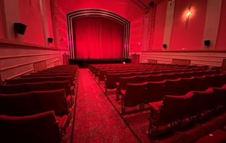 Inside the screen room with red deco red carpet and red seating