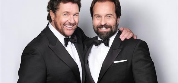 Two men in black and white suits on a plain background