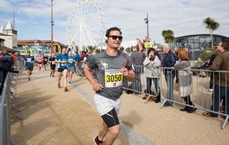 Man looking happy with sunglasses running with the big wheel behind him