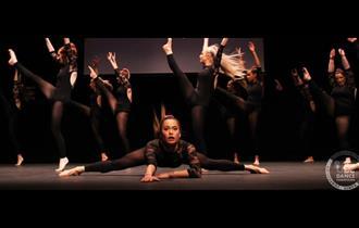 Dancers dressed in black leotards kick their legs above their heads. Principal dancer lies in splits, centre stage.