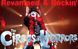 Man dressed in black and red with stage lights behind him and a logo of the Circus of Horrors