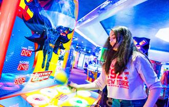 Girl plays a batman themed game in the amusements on Bournemouth Pier