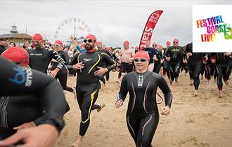 Group of people in swimming gear running on the beach