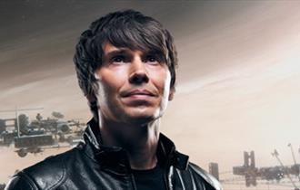 Professor Brian Cox in a leather jacket looking slightly upwards
