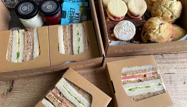 Box filled with afternoon tea, sandwiches and scones