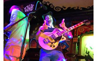 Man holding thumbs up with guitar and coloured lighting