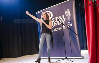 Lady stands on stage with hand in the air