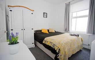 Fresh modern bedroom with yellow pillows and throw