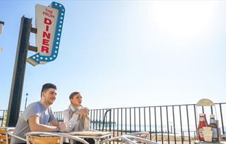 Two people sitting outside the diner with a blue sky above.