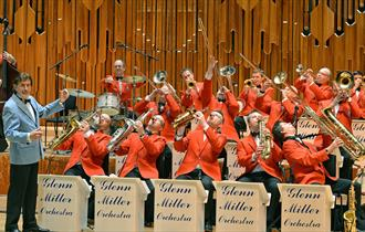 Orchestra players in red clothing playing instruments