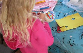 The image is of the back of the head of a blonde-haired child wearing a pink jumper, making a Halloween decoration at a table with a blue table cover