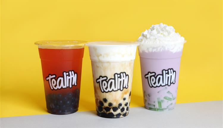 A shot of three bubble teas on a yellow background; one red, one creamy and one purple with foam.