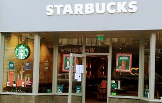 The front of Starbucks in Westbourne with an open door and large grey name above the entrance.
