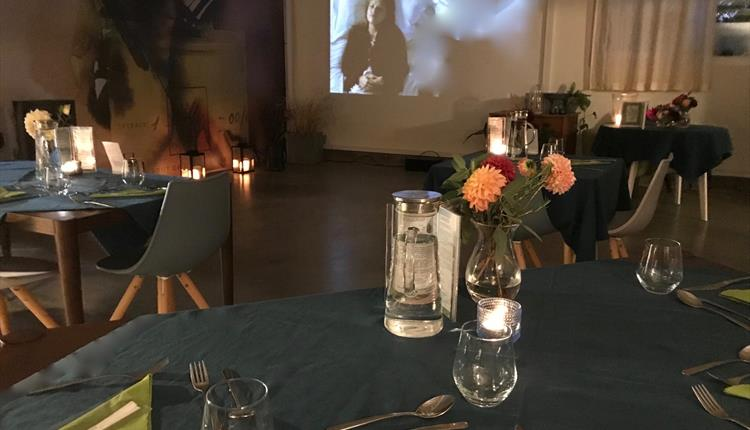 Tables made ready for a dinner in front of the cinema projection screen.