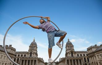 Man standing in a large hoop reaching out
