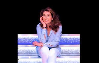 Jane Mcdonald sat on a white stage wearing lilac shirt and white trousers, chin in hand