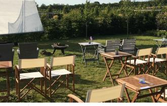 chairs and tables outside in a pretty field in front of a cinema screen